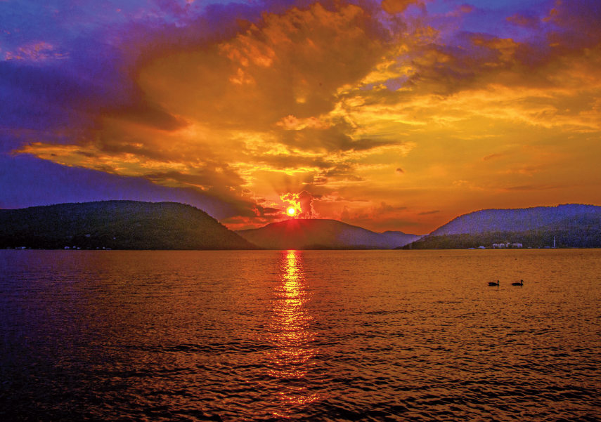Orange sunset going down over mountains on the other side of the Hudson River