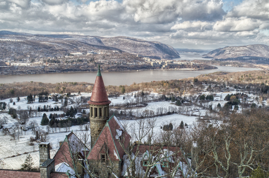 Old stone mansion in foreground overlooking the Hudson River after a snow fall
