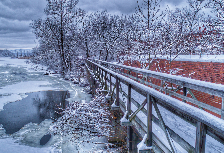 Walkway next to red brick wall along frozen water on a cold winter day