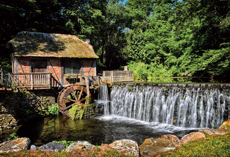 Brick building with water wheel next to a dam with water running over it