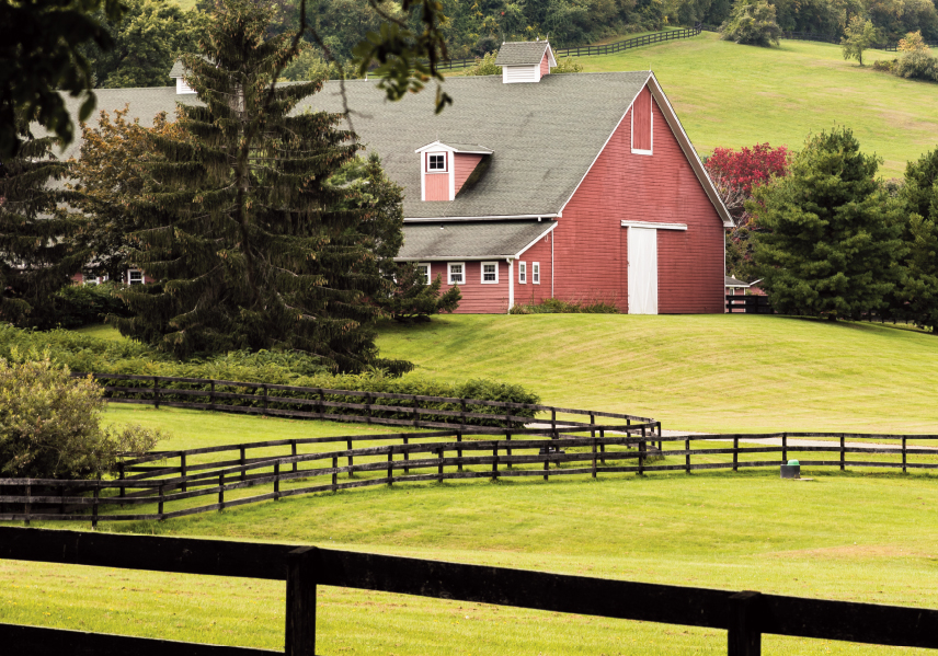 Red barn surrounded by cut green lawn, trees and fence.
