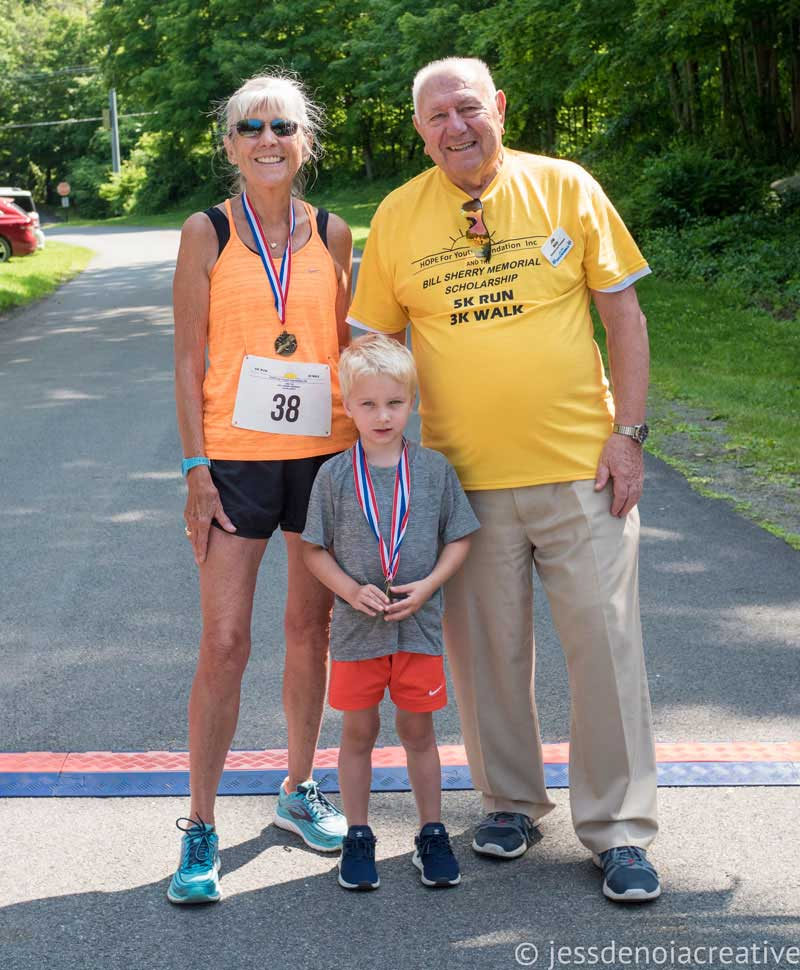 Jim Witt wearing yellow t-shirt with young blonde hair boy and older female runner. Oldest and youngest 5K participants.