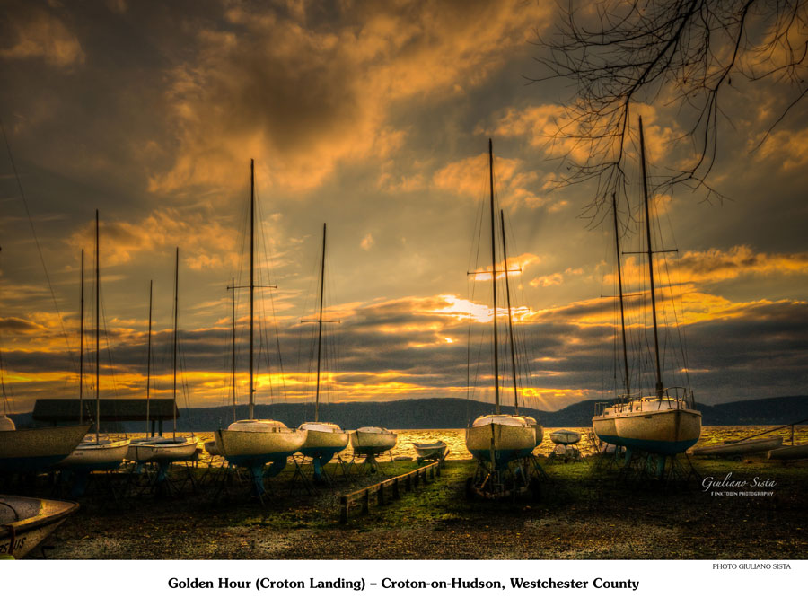 Sailboats on land lined up in rows. Sun setting in the background.
