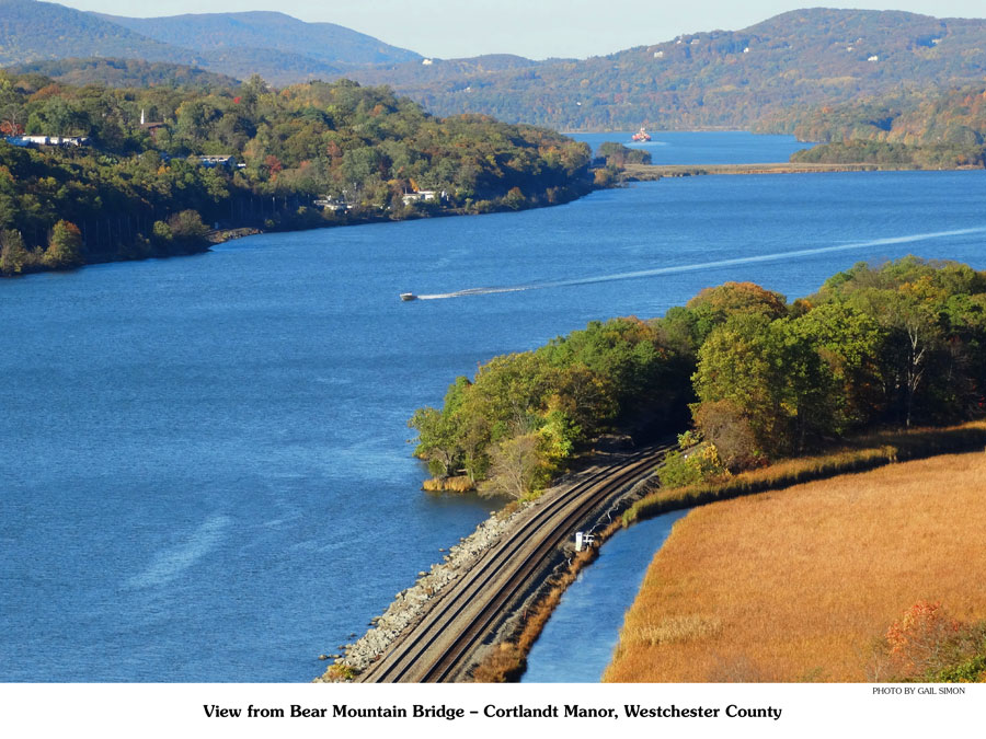 View of the Hudson River facing north from the Bear Mountain Bridge. One boat in the middle of the river and mountains in the background.